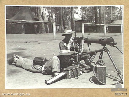 WONDECLA, QLD. 1944-04-05. NX124996 PRIVATE C. PARKINSON, RIGHT (1) AND NX69112 PRIVATE W.T. SHELDON (2) OF THE 2/2ND INFANTRY BATTALION WITH A VICKERS GUN MOUNTED ON A BREN GUN TRIPOD. THIS MODIFICATION EFFECTS A 30 POUND SAVING IN WEIGHT.