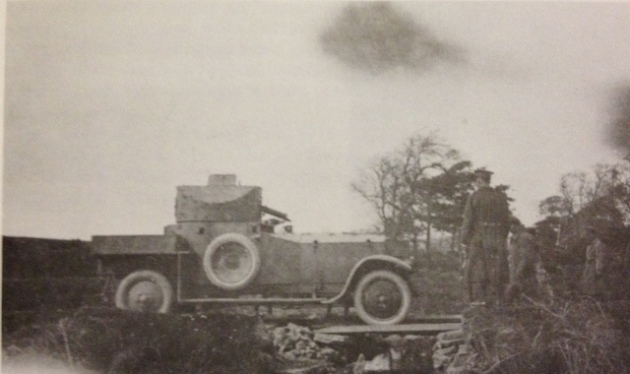 A Rolls Royce armoured car edges gingerly over a makeshift bridge to cross a culvert destroyed by the IRA in 1921. Members of the 28th look on.
